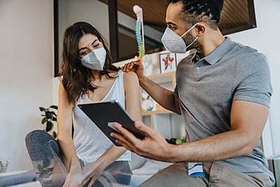 Male physiotherapist and female patient wearing protective face mask discussing over digital tablet in practice - p300m2276830 by Mareen Fischinger