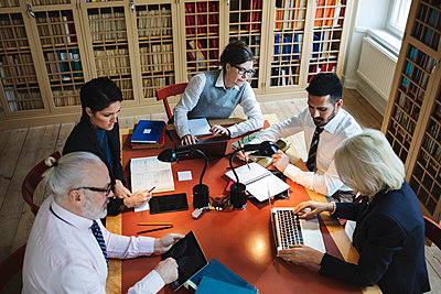 High angle view of professionals working at table in law library - p426m1148101 by Maskot