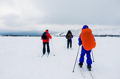Caucasian people cross-country skiing in field - p555m1491031 by Aleksander Rubtsov