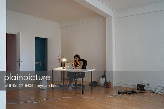 A woman working in an empty office - p1610m2216435 by myriam tirler
