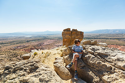 Boy hiking to the top of Chimney Rock landmark in a protected canyon landscape  - p1100m2220400 by Mint Images