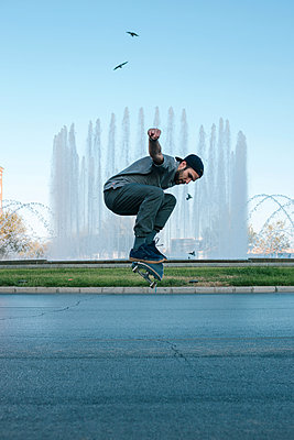 Side view of man performing stunt while skateboarding on road against fountain at park - p1166m2025480 by Cavan Images