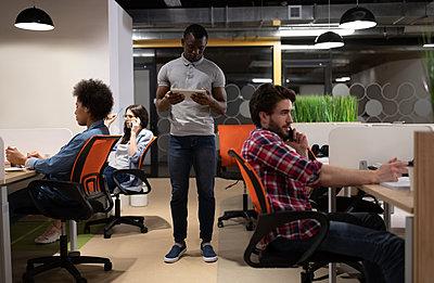 Black man using tablet near colleagues speaking on phones - p1166m2234846 by Cavan Images