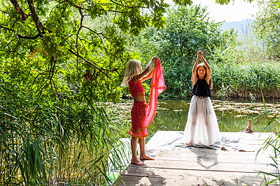 Two girls standing on jetty at a pond in fancy dresses - p300m2030332 von Tom Chance