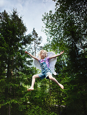 Girl wearing wings and jumping in forest - p42916135f by Christoffer Askman