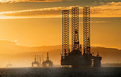 Oil drilling rigs out in the ocean with a view of the coastline and golden sunset; Cromarty, Invergordon, Scotland - p442m1139274 by John Short