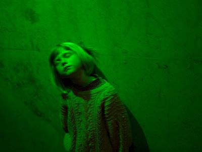 Blondes Mädchen in grünes Licht getaucht - p945m1444655 von aurelia frey