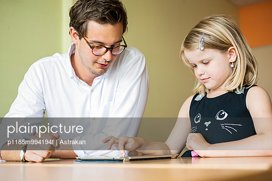 Male teacher watching girl painting on digital tablet in classroom