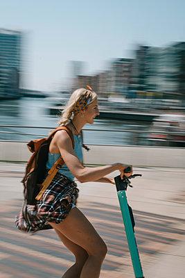 Junge Frau unterwegs mit dem E-Scooter - p299m2108619 von Silke Heyer