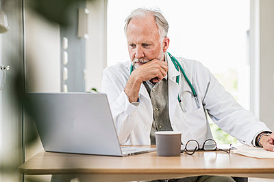 Mature male doctor looking at laptop at desk - p300m2293822 by Uwe Umstätter