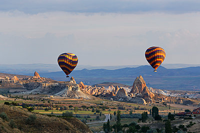 Turkey, Eastern Anatolia, Cappadocia, two hot air balloons hoovering over tuff rock formations at Goereme National Park - p300m941073f by Martin Siepmann