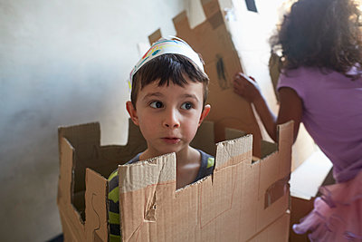 Boy wearing crown playing with cardboard boxes by friend against wall - p301m1579643 by Liesel Bockl