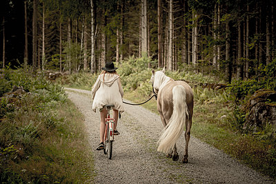 Woman on bike and horse on dirt track - p312m1471765 by Caluvafoto