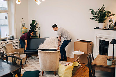 Man and woman arranging sofa in living room - p426m1542754 by Maskot