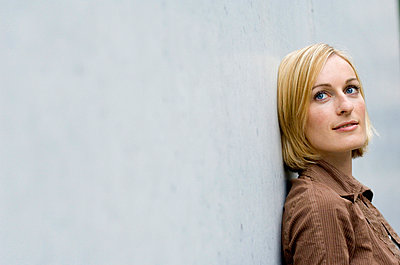 Young woman leaning against concrete wall - p473m937198f by STOCK4B-RF