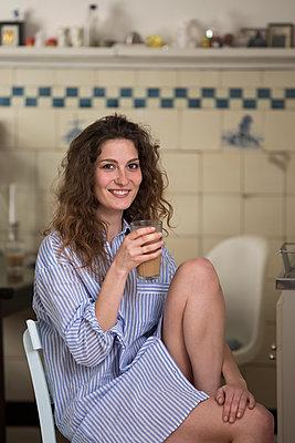 Junge Frau trinkt einen Milchkaffee - p788m1424941 von Lisa Krechting