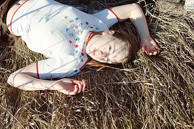 Junge Frau liegt auf dem Rücken im Gras - p956m1515494 von Anna Quinn