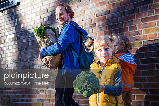 Girl carrying broccoli while father with vegetable bag standing against son - p300m2275454 by Irina Heß
