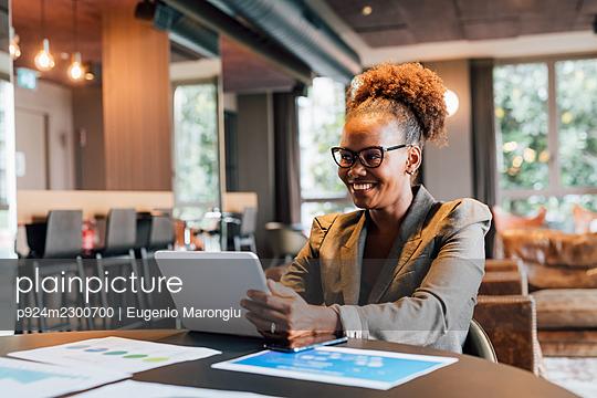 Italy, Smiling businesswoman using digital tablet in creative studio - p924m2300700 by Eugenio Marongiu