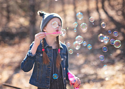 Young Girls Blowing Bubbles Outdoors - p1166m2208445 by Cavan Images