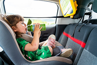 Toddler girl sitting on a car seat with a mirror drinking water - p300m2140380 by Gemma Ferrando