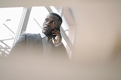 Portrait of young businessman in front of window on the phone - p300m2167316 von Kniel Synnatzschke
