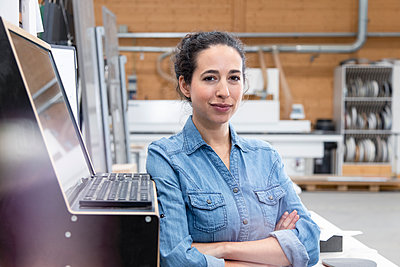 Confident businesswoman standing by control panel at factory - p300m2265979 by Florian Küttler