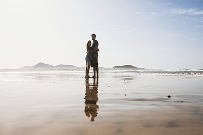 Full length of loving couple embracing at beach on sunny day - p301m1148335 by Sven Hagolani