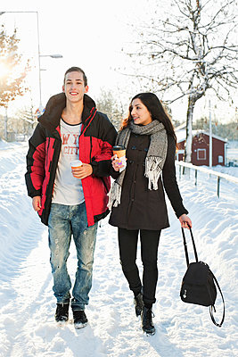 Young friends walking on snow covered street - p426m766628f by Maskot