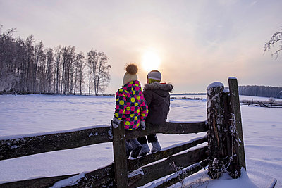 Boy and girl sitting on fence in snow covered landscape, rear view - p429m2069325 by Aliyev Alexei Sergeevich