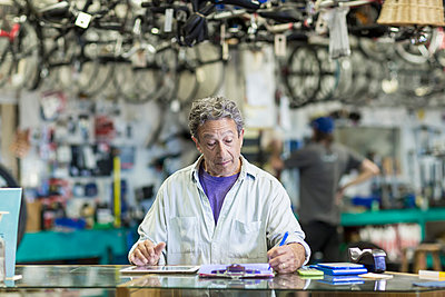 Caucasian man in bicycle shop writing on clipboard - p555m1521376 by Marc Romanelli
