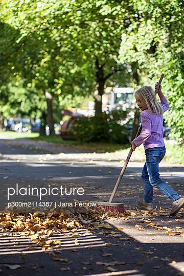 Girl sweeping leaves on pavement - p300m2114387 von Jana Fernow