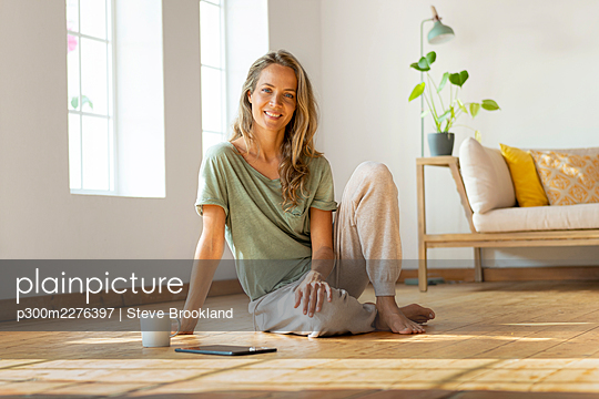 Happy woman sitting on floor by digital tablet and mug at home - p300m2276397 by Steve Brookland