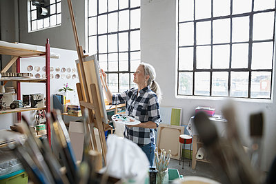 Female painter with palette painting at canvas in art studio - p1192m1490261 by Hero Images