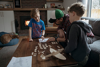 Father and sons assembling model airplane, reading instructions in living room - p1192m1567346 by Hero Images