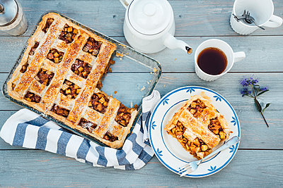 Homemade apple tart on plate and cup of black tea - p300m2042080 by Ina Peters