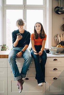 Full length of male and female friends with mobile phones sitting at kitchen counter - p426m1555874 by Maskot