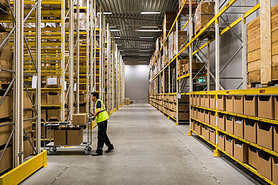 Full length side view of young warehouse worker pushing cart on aisle in industrial building - p426m2018858 by Maskot