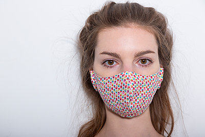 Young woman wearing protective face mask, portrait - p975m2230860 by Hayden Verry