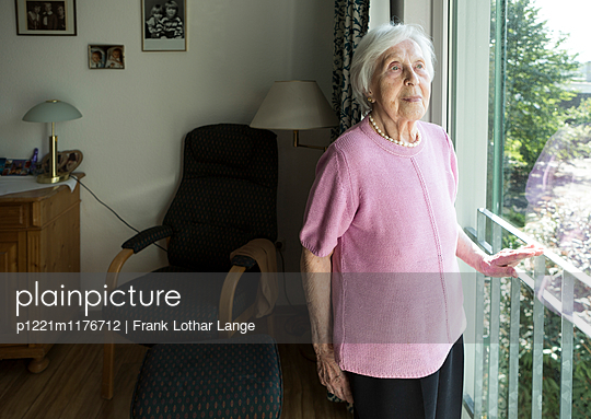 Old woman is looking out the window - p1221m1176712 by Frank Lothar Lange