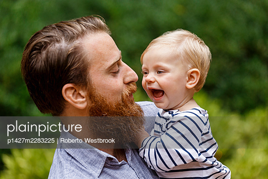 Portrait of father and baby girl, outdoors, laughing - p1427m2283225 by Roberto Westbrook