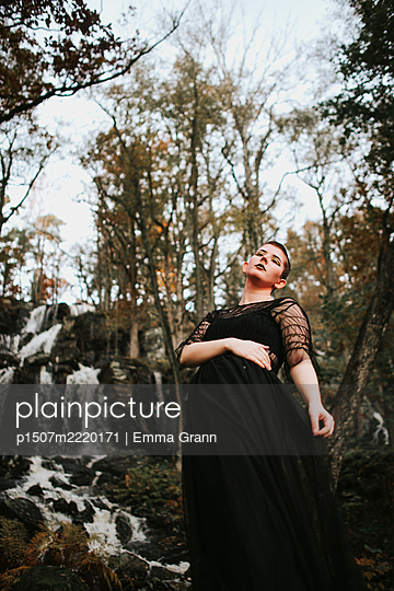 Young woman in black dress at waterfall - p1507m2220171 by Emma Grann
