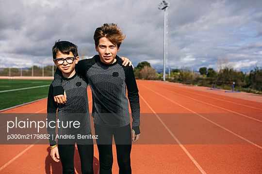 Boys standing on running track, with arms around - p300m2179852 by Andrés Benitez