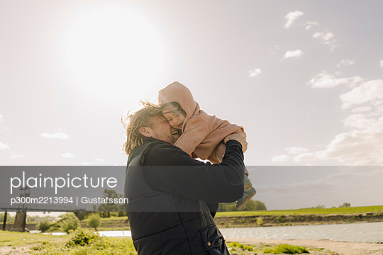 Father nuzzling daughter while standing near river bank on sunny day - p300m2213994 by Gustafsson