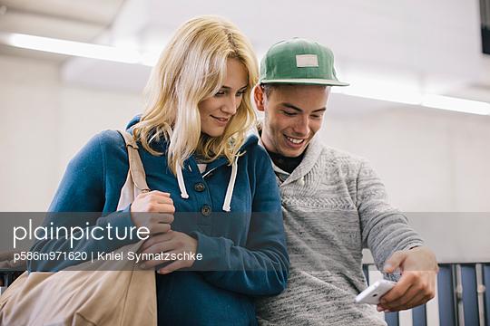 Zwei junge Leute mit Smartphone - p586m971620 von Kniel Synnatzschke