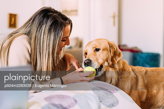 Italy, Young woman and dog playing at home - p924m2283035 by Eugenio Marongiu