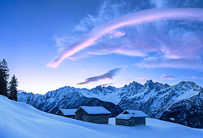 Stunning clouds above huts at sunrise. Soglio, Bregaglia Valley, Canton of Grisons, Switzerland, Europe. - p651m2135806 by Francesco Bergamaschi
