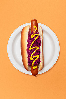 High Angle View of Hotdog with Purple Sauerkraut and Mustard on Roll Against Orange Background - p694m2031436 by Novo Images
