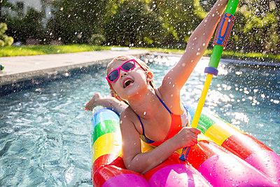 Girl in bikini on inflatable playing with water gun in outdoor swimming pool - p924m1404256 by Sasha Gulish