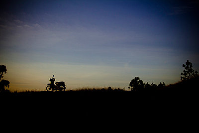 A motorbike is parked in a meadow. Countryside of Hue at dusk. Vietnam, Asia 2012. - p934m832597 by Francis Roux photography